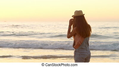 Woman taking photo with camera in the beach 4k - Woman...