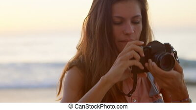 Woman taking photo with camera in the beach 4k
