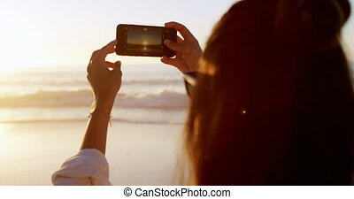 Woman taking photo with mobile phone in the beach 4k