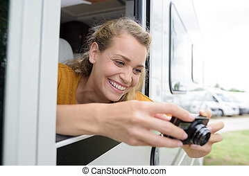 woman taking photograph from campervan window