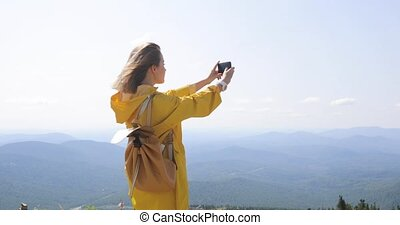 Woman taking photograph in mountains with smartphone photographing scenic landscape nature background view enjoying vacation travel adventure