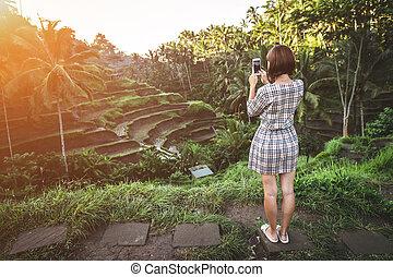 Woman taking photos on a beautiful rice field during sunrise. Bali island.