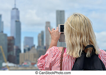 Woman taking picture New York city skyline