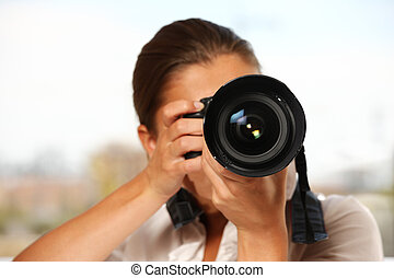 Woman taking pictures - A young woman taking pictures over ...