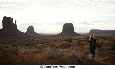 woman taking pictures in Monument Valley with a camera.