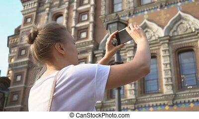 Woman taking pictures of Church of the Savior on Blood with smartphone.