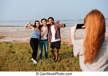 Woman taking pictures of her friends with mobile phone outdoors