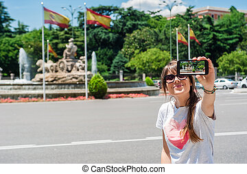 Young tourist woman taking picture with Cibeles Fountain, one of the most famous monuments of architecture of Madrid located on the Cibeles square in the Centre of Madrid, Spain