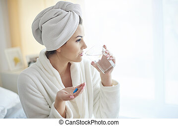 Woman taking pill at the morning