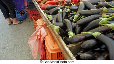 Woman taking plastic bag. Aubergines on foreground