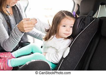 Woman Taking Precautions For Daughter In Car