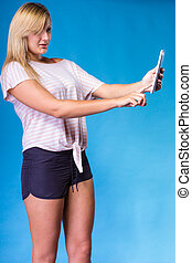 Woman taking self picture with tablet
