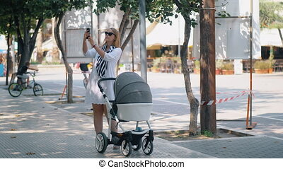 Woman taking selfie and photo of baby during the walk