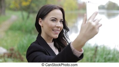 Woman taking selfie near pond - Beautiful woman in black...