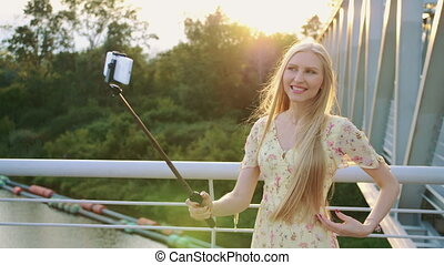 Woman taking selfie on bridge. Cheerful pretty blonde woman standing on pedestrian bridge and taking selfie with monopod in sunset.
