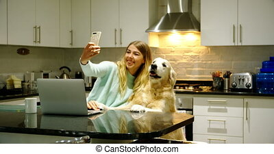 Woman taking selfie with her dog in kitchen 4k