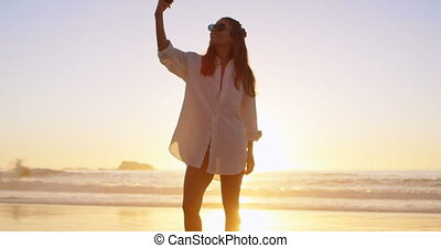 Woman taking selfie with mobile phone in the beach 4k