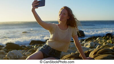 Woman taking selfie with mobile phone on the beach 4k