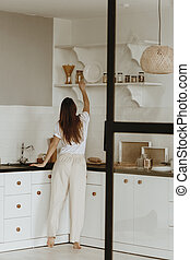 Woman taking something from shelf in kitchen.