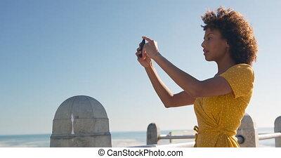 Woman taking video at beach