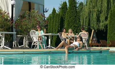 Woman taking video call at terrace by the pool and group of teens talking at another table while young woman relaxes on the pool edge