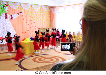 Woman taking video of children's morning party. Children on matinee at kindergarten