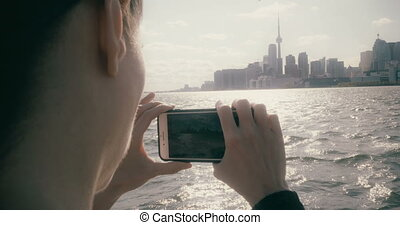 Woman taking video of the Toronto skyline - A pretty woman...