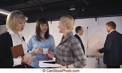 Unity of adult and clever business person standing inside office with loft interior working place. Three woman talking about new business project on special seminar in company or agency