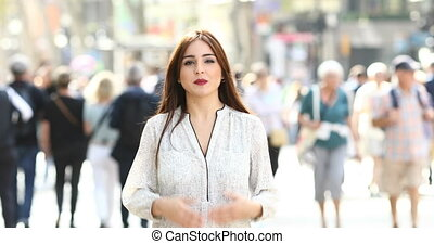 Woman talking at camera in the street