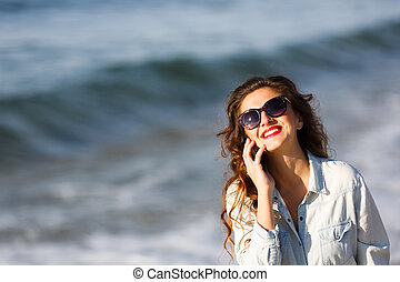Woman talking by the phone on the beach at autumn time
