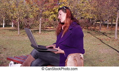 Woman talking on a laptop in the Park on a bench