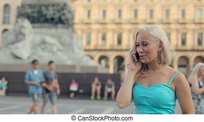 Woman talking on a mobile phone in Duomo Square near horse statue