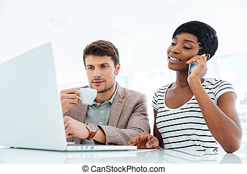 Woman talking on cell phone and working with serious man