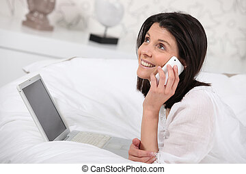 Woman talking on her mobile phone and using her laptop in bed