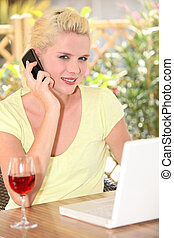 Woman talking on her mobile phone in front of her laptop and a glass of wine