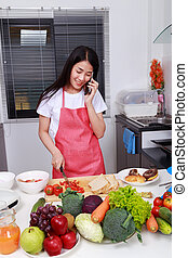 woman talking on mobile in kitchen room