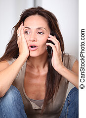 Woman talking on mobile phone at home