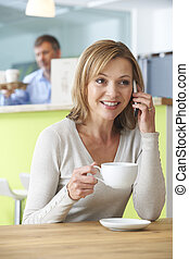 Woman Talking On Mobile Phone In Coffee Shop