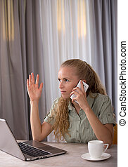Woman talking on mobile phone in front of laptop