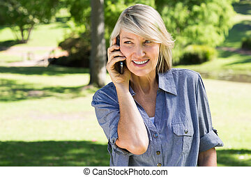 Woman talking on mobile phone in park