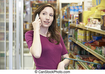 Woman Talking On Mobile Phone In Supermarket
