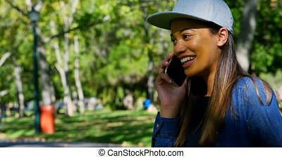 Woman talking on mobile phone in the park 4k