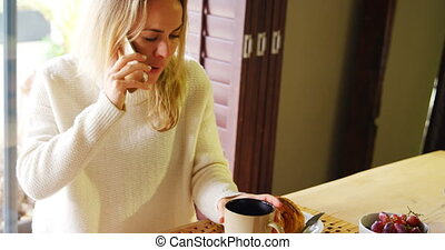 Woman talking on mobile phone while having coffee 4k - Woman...