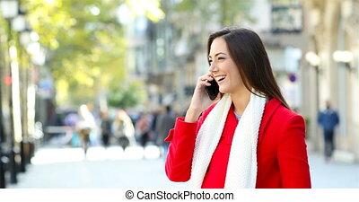 Woman talking on phone in the street in winter