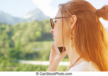 Woman talking on phone on background of summer mountains.
