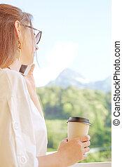 Woman talking on phone on mountain resort.