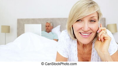 Woman talking on phone with husband using laptop in bed at...