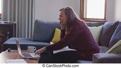 Woman talking on smartphone while using laptop at home