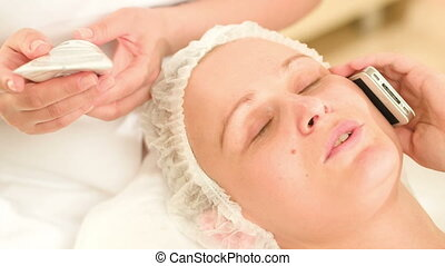 Woman talking on the phone at beauty spa