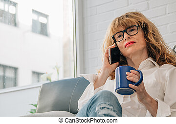 woman talking on the phone at home with cup of coffee